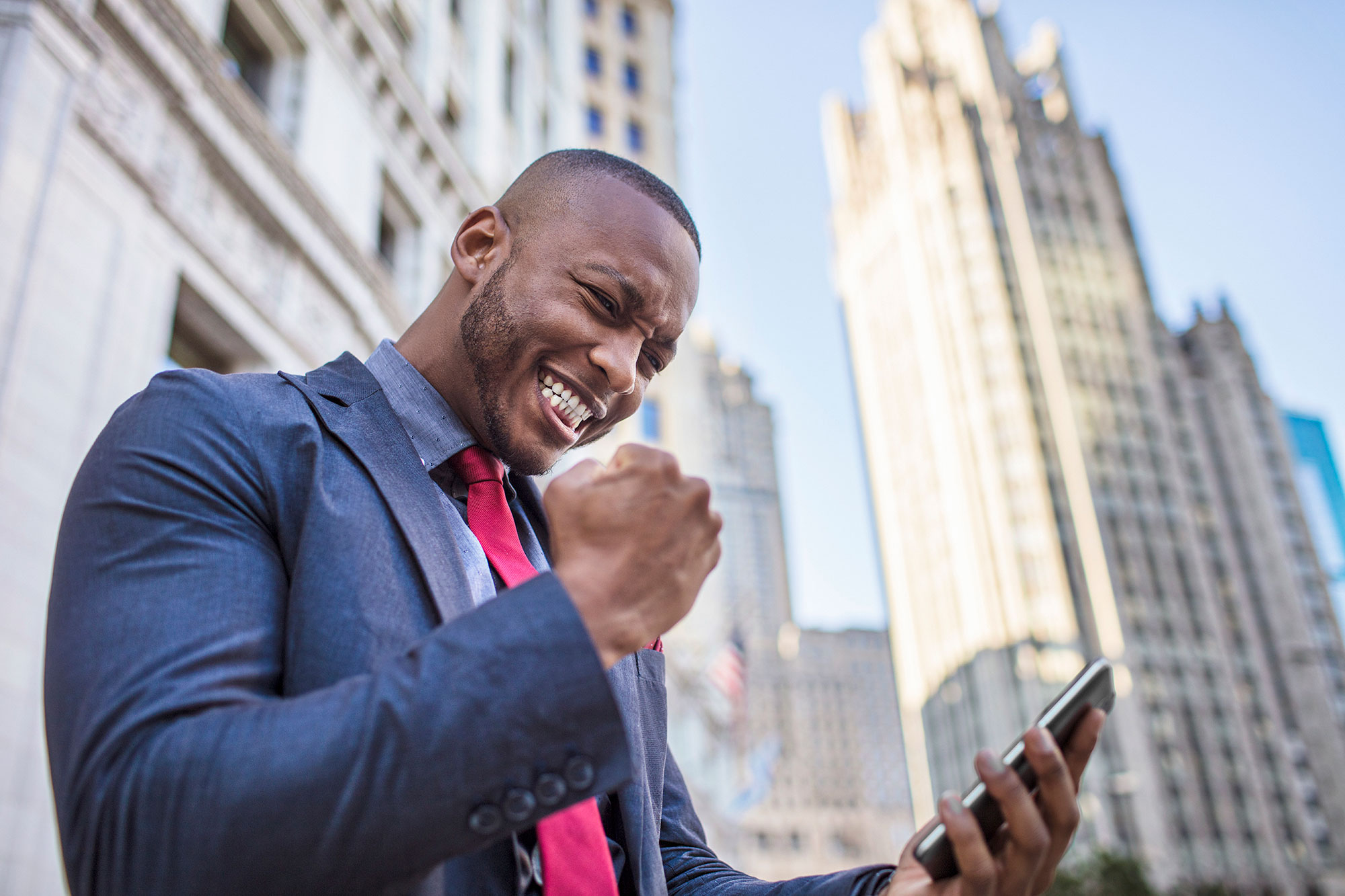 business-man-holding-mobile-phone-celebrating-smiling-fist-pump