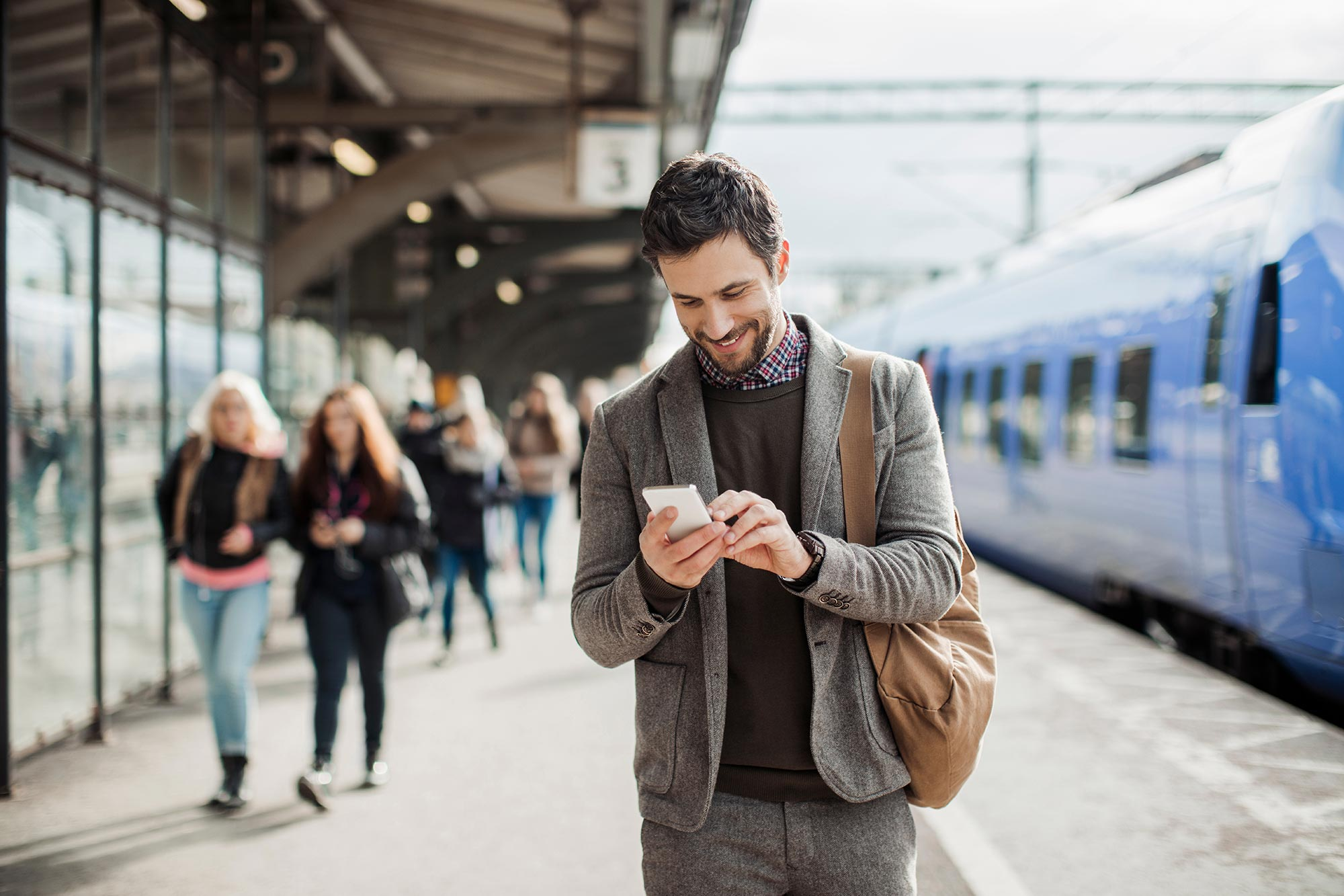 businessman-using-mobile-phone-at-train-station