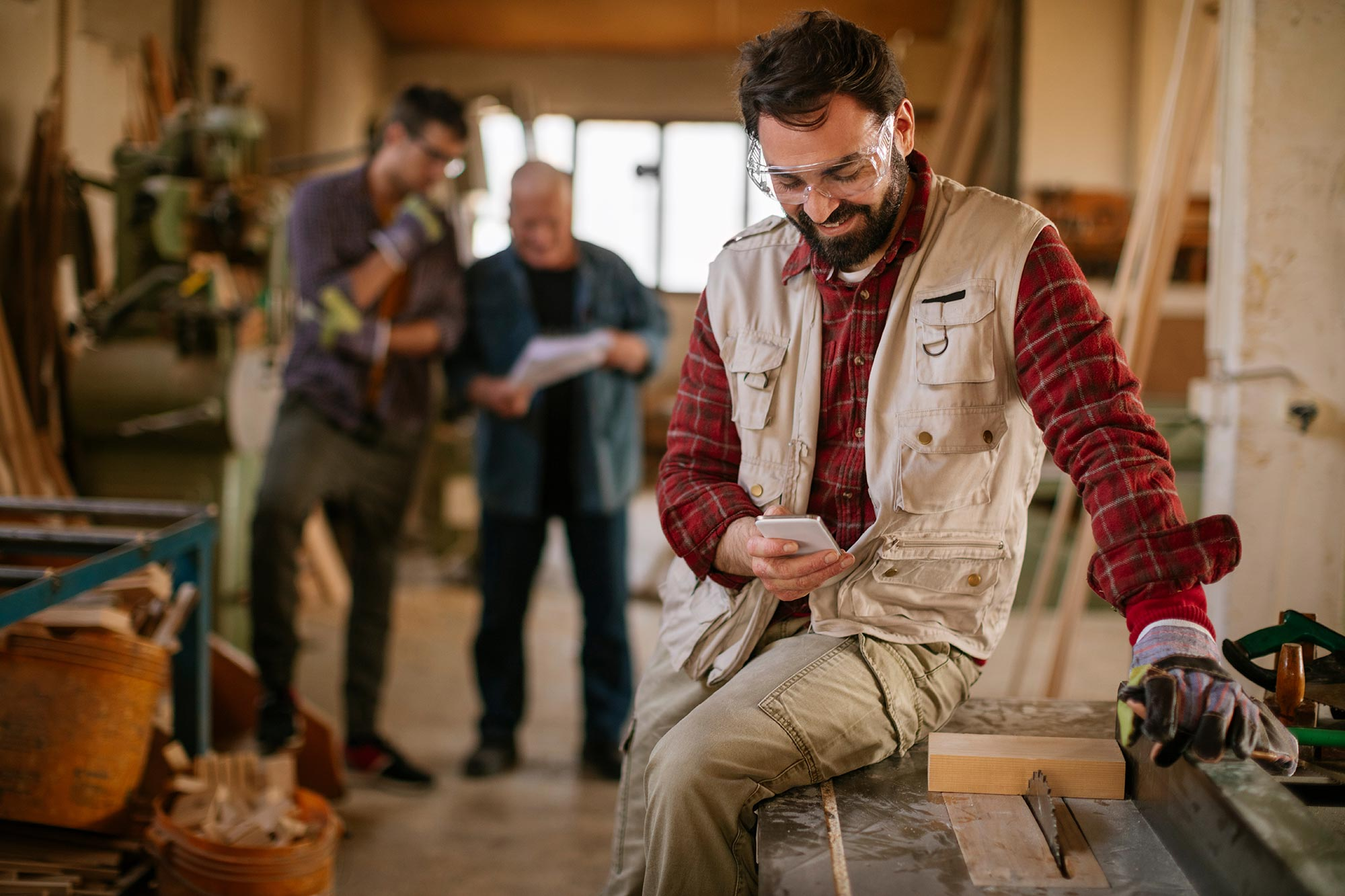 carpenter-man-with-mobile-phone-in-workshop