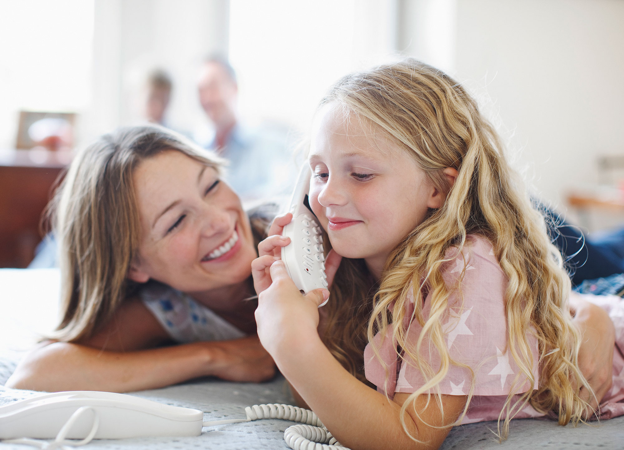 family-mother-daughter-landline-telephone-smiling