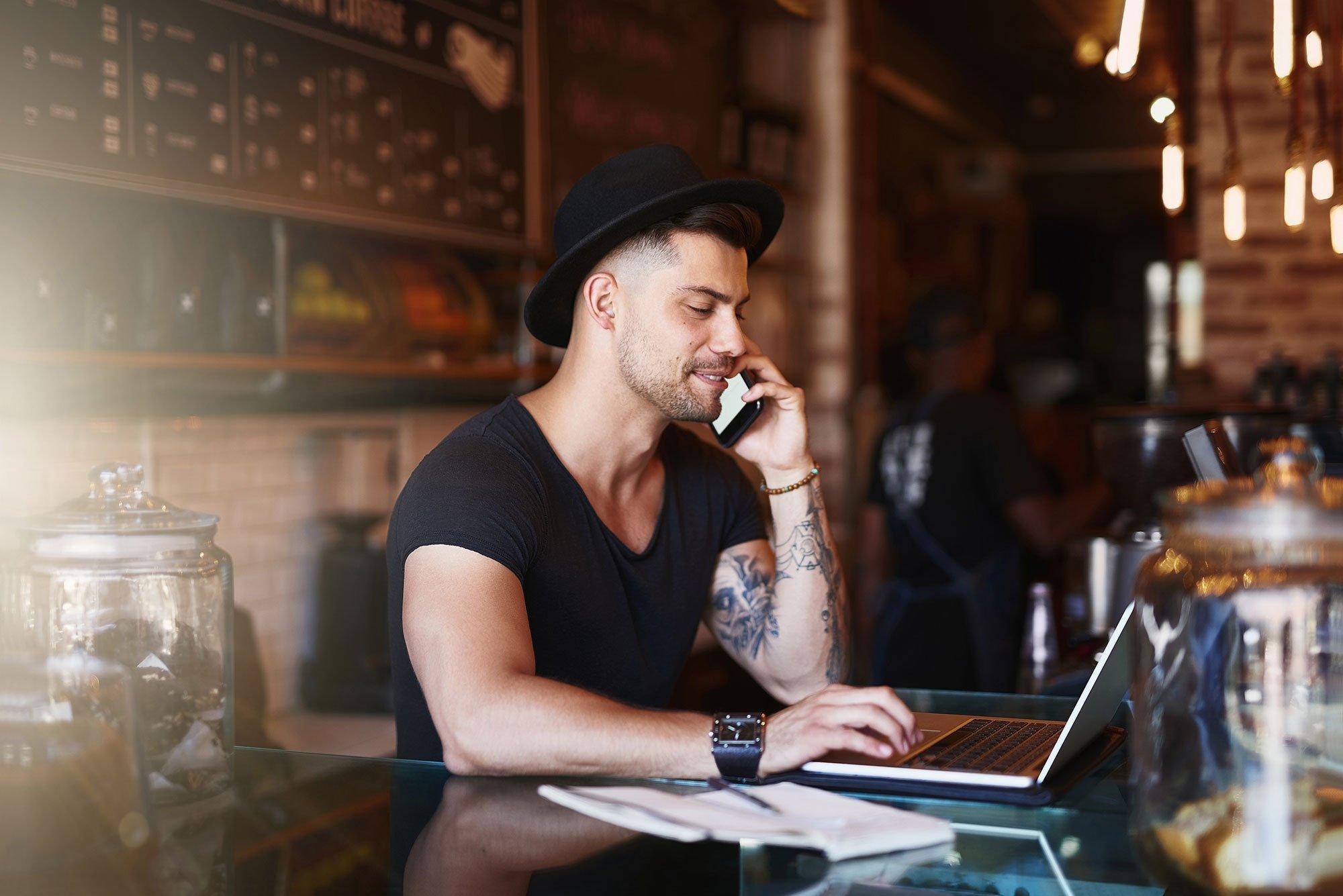 man-wearing-hat-tattoos-behind-bar-using-mobile-phone-and-laptop