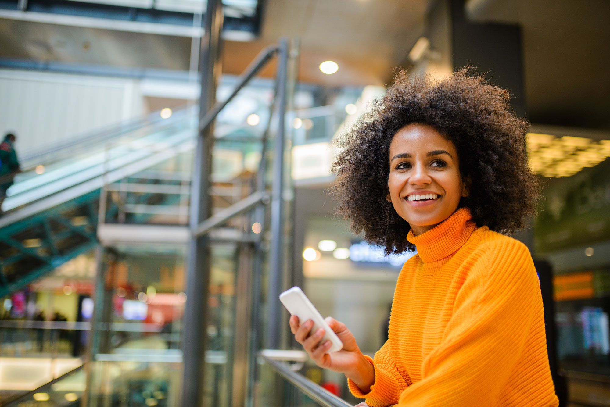 woman-holding-smartphone-in-airport-smiling