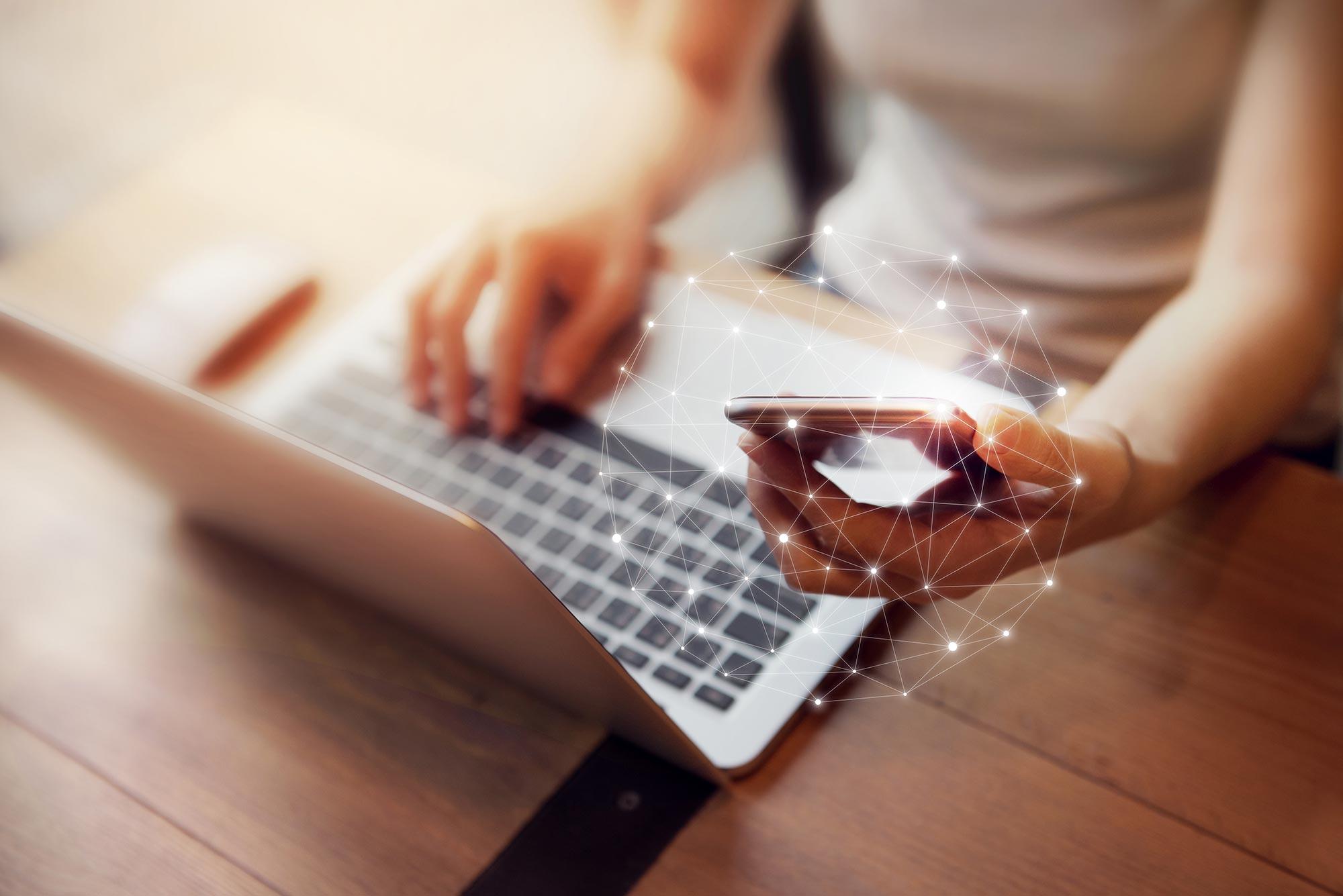 woman-holding-smartphone-using-laptop-connectivity.jpg