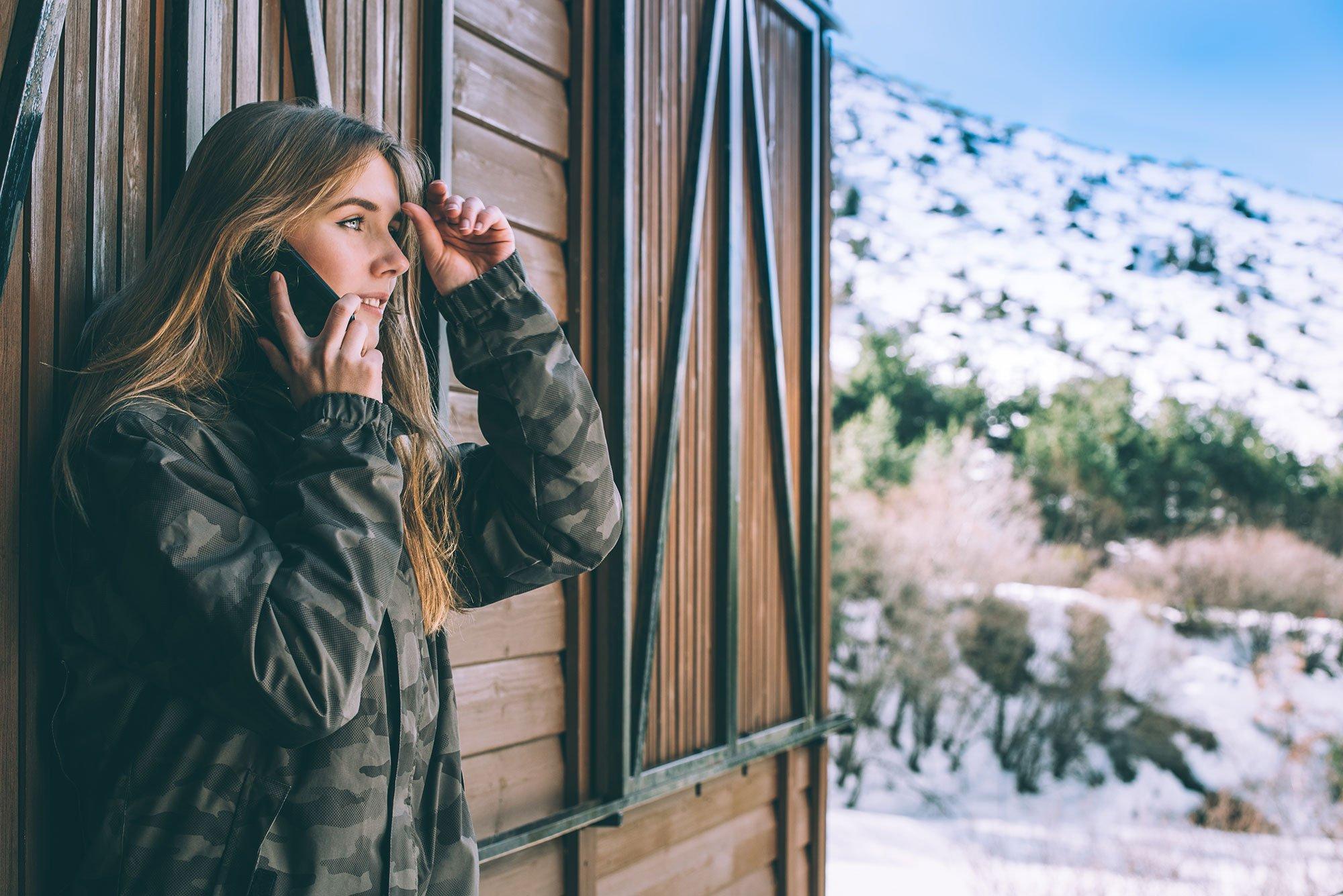 woman-mobile-phone-rural-cabin-mountain-winter-snow