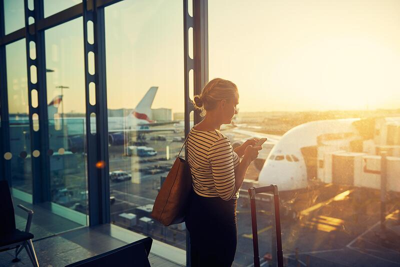 woman-using-smartphone-at-airport-with-planes.jpg