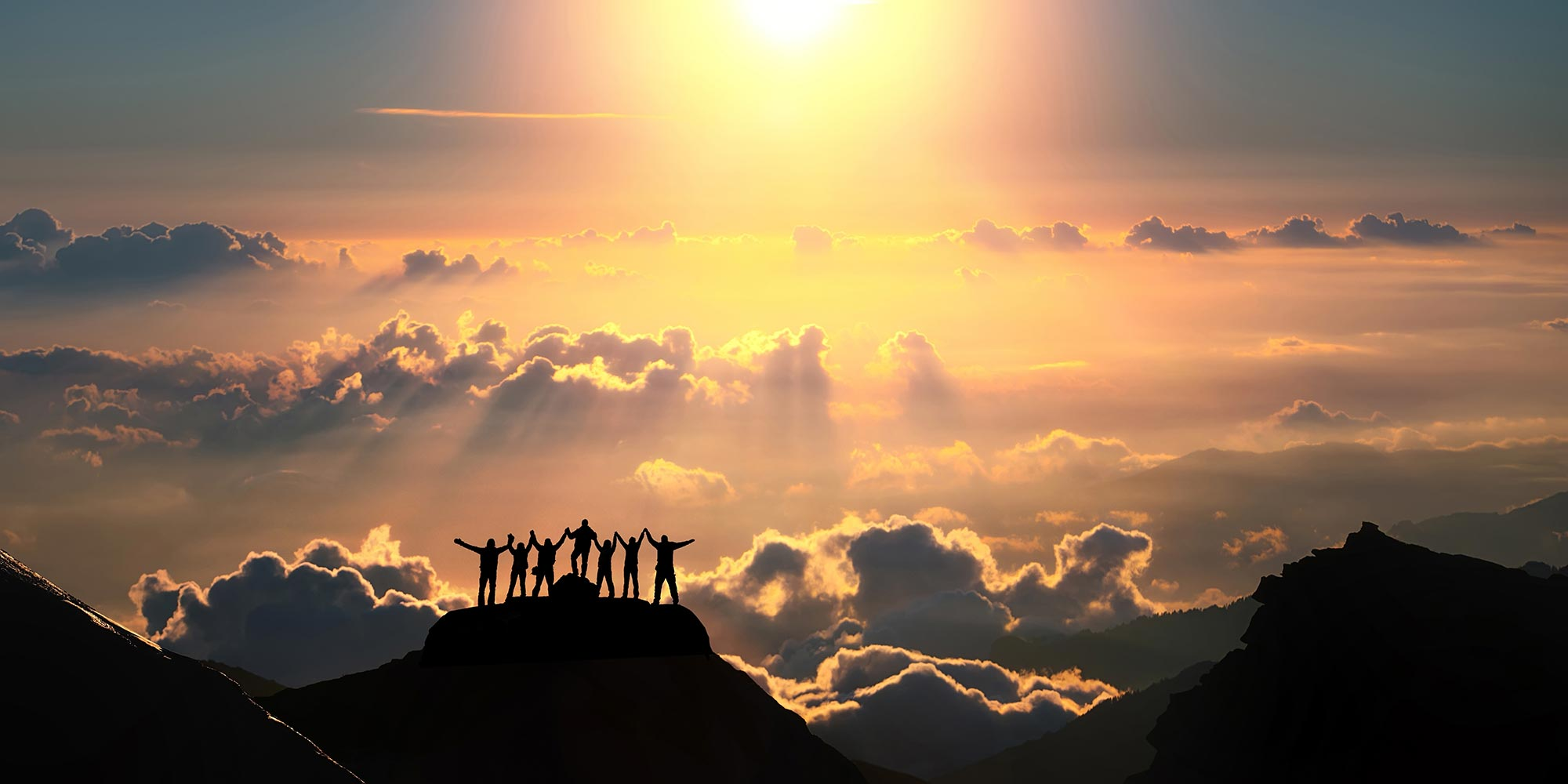 group-of-people-silhouette-on-mountain-clouds-sunset.jpg
