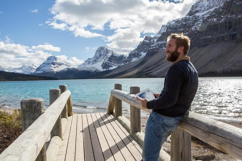 man-holding-tablet-at-lake-with-snowy-mountains.jpg