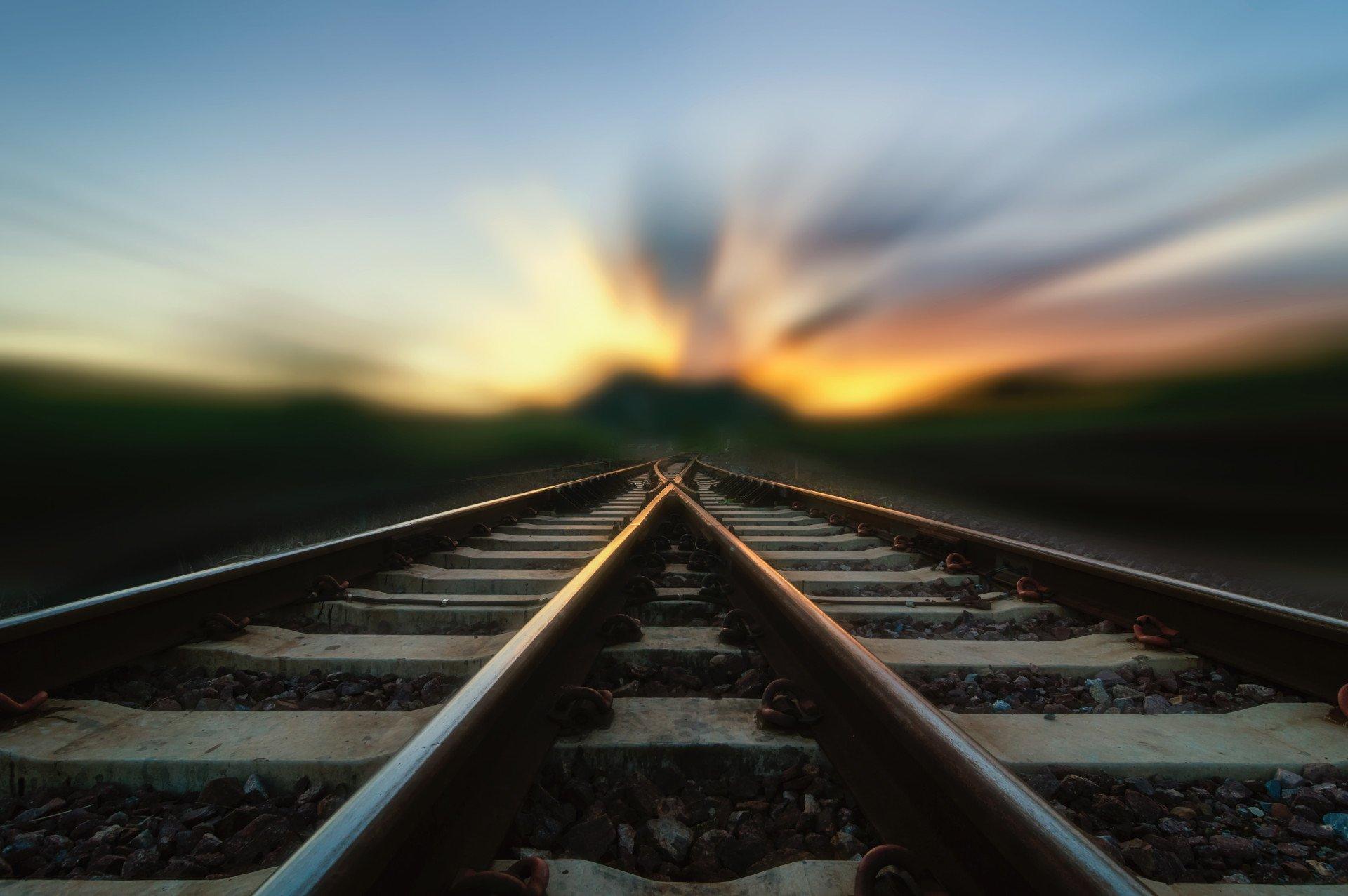 rail-lines-merge-converge-sunset-blur