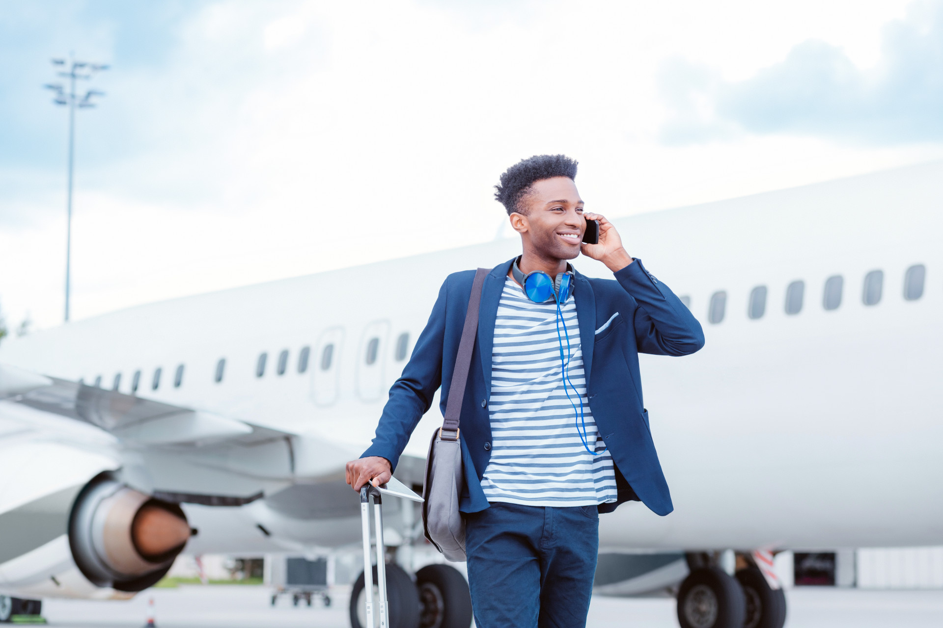 young-businessman-airplane-suitcase-phone